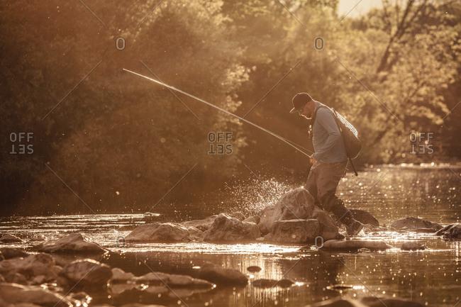 Fisherman stepping ankle deep in sunlit river, Mozirje, Brezovica, Slovenia