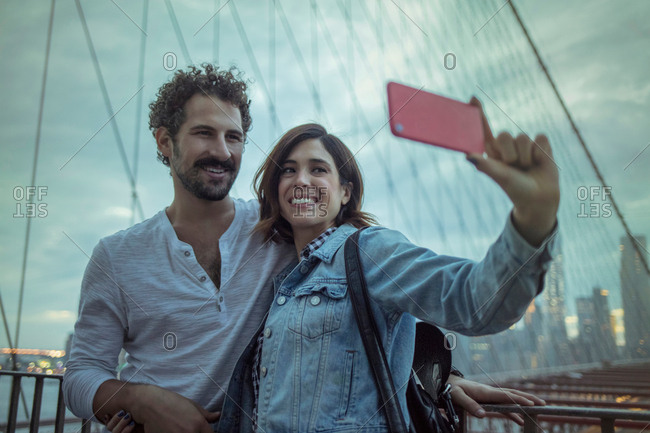 Couple on Brooklyn bridge taking selfie, New York, United States, North America