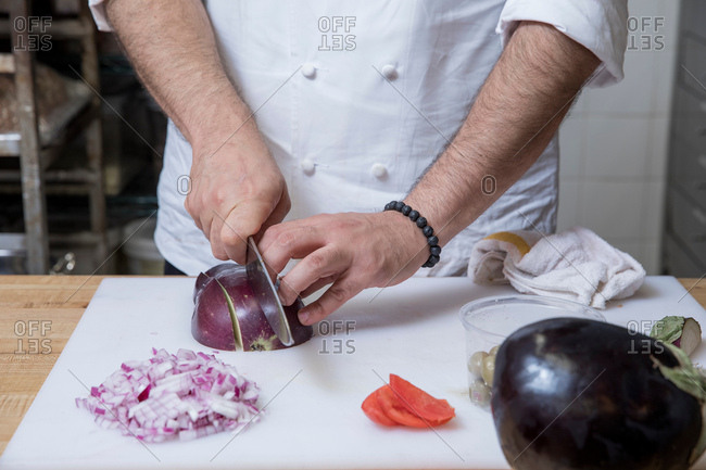 Cropped view of chef slicing red onion