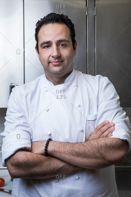 Portrait of chef in commercial kitchen, arms crossed, looking at camera