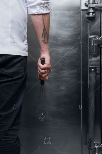 Cropped view of tattooed chef holding whisk
