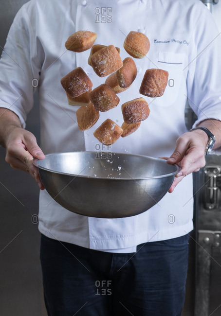 Cropped view of chef tossing doughnuts and sugar in mixing bowl