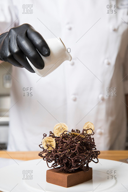 Chef pouring cream over chocolate nest cake decoration on cake