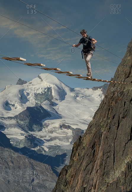 Mature male climber stepping across wire rope bridge, Jegihorn, Valais, Switzerland