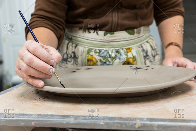 Potter painting motifs on platter