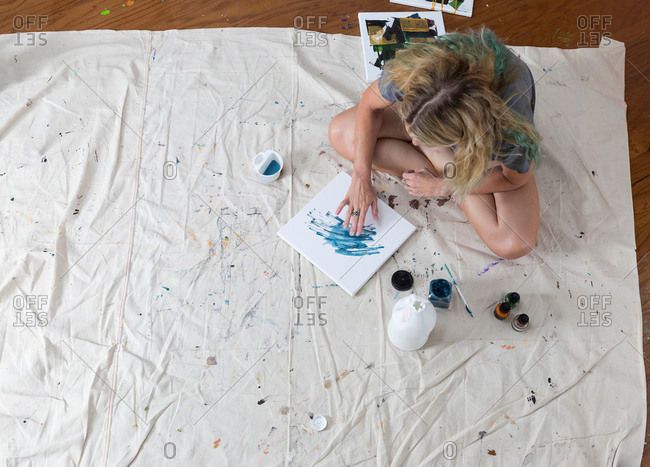 Overhead view of female artist sitting on dust sheet finger painting abstract canvas