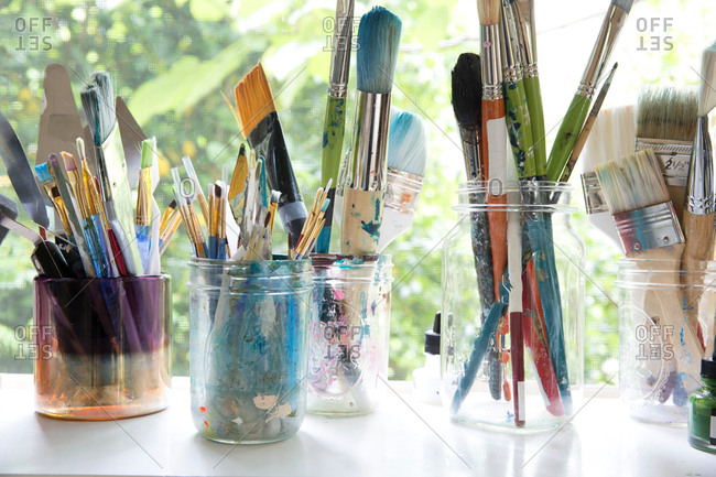 Row of jars with variety of artist paintbrushes on window sill  of artists studio