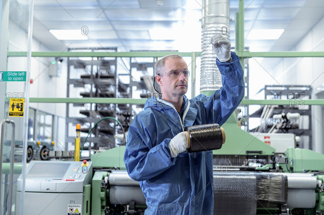Operator with bobbin of carbon fibre in carbon fibre production facility