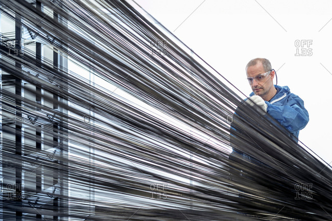 Operator with carbon fibre thread on loom in carbon fibre production facility