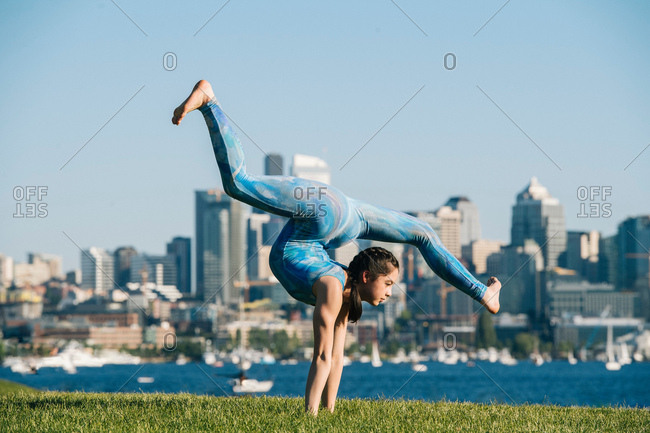Teenage girl outdoors, balancing on hands in yoga position