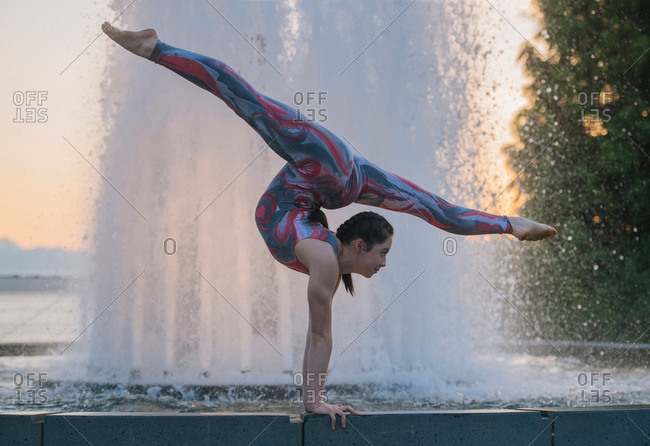 Teenage girl beside fountain, balancing on hands in yoga position