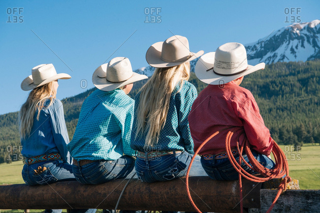 Rear view of cowboys and cowgirls on fence, looking away, Enterprise, Oregon, United States, North America