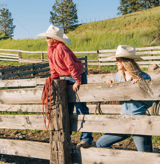Cowboy and cowgirl wearing cowboy hat leaning on fence, looking away, Enterprise, Oregon, United States, North America
