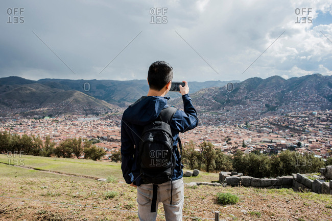 Man photographing view from Sacsayhuaman, using smartphone, Cusco, Peru, South America