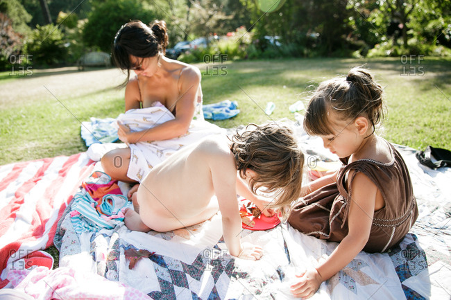 Family relaxing on blankets on grass