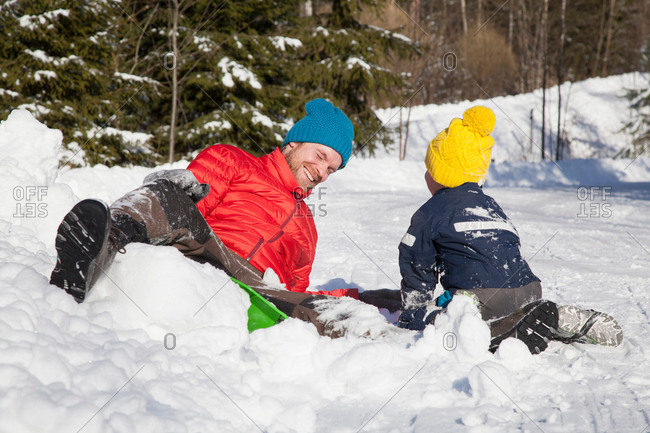 Man and son laughing after falling from toboggan in snow covered landscape
