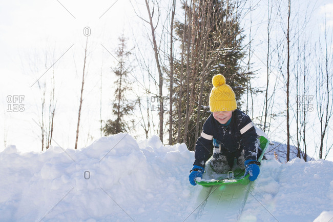 Boy in yellow knit hat tobogganing on snow covered hill