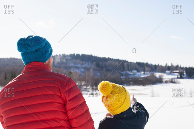Rear view of man and son looking out and pointing over snow covered landscape