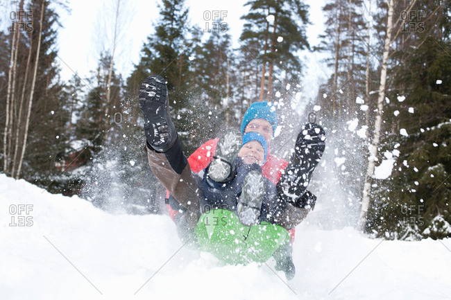 Man and son on speeding toboggan in snow covered forest