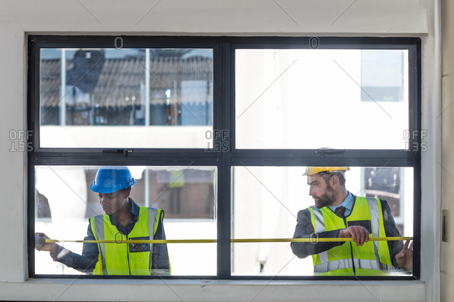 Colleagues in hard hats and high viz jackets measuring window