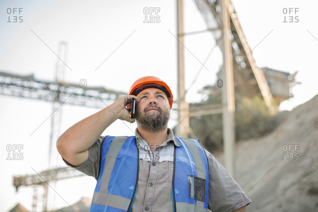 Quarry worker in quarry, using smartphone, looking up