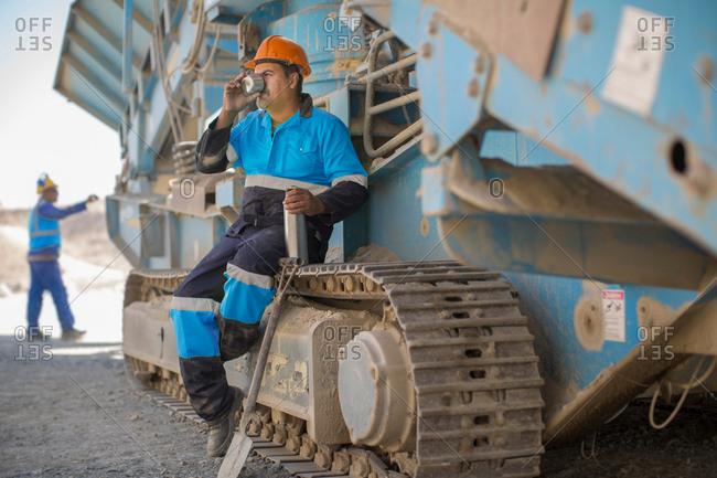 Quarry worker resting on heavy machinery, drinking from flask cup