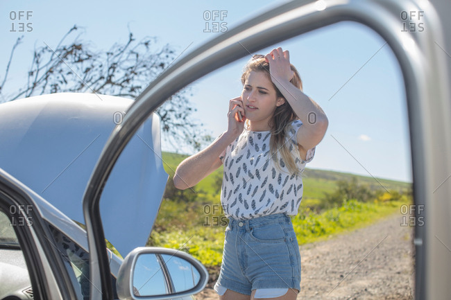 Young woman beside broken down car, using smartphone