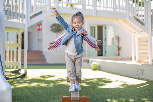 Girls at preschool, portrait balancing on balance beam in garden