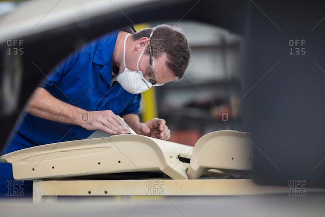 Car mechanic sanding car door in repair garage