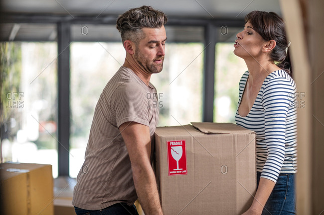 Couple in unfurnished home, carrying box of fragile belongings