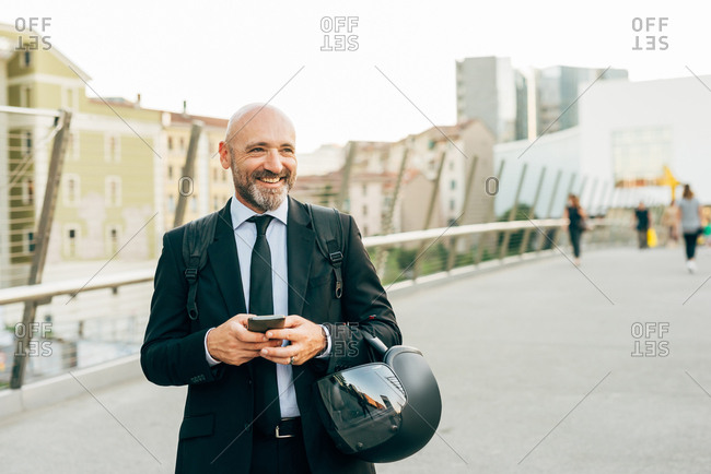 Mature businessman standing on bridge, holding smartphone and motorcycle helmet