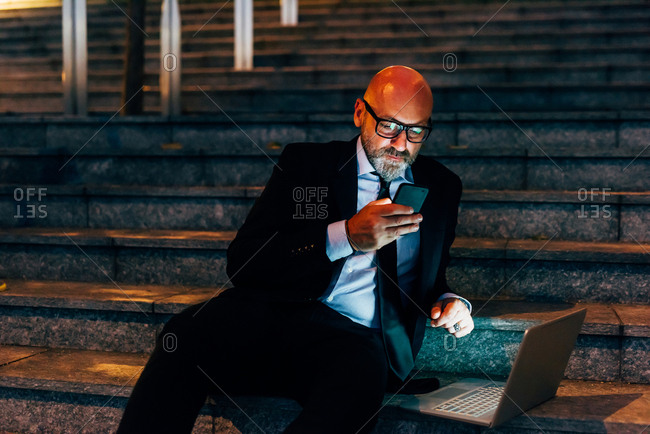 Mature businessman outdoors at night, sitting on steps, using smartphone, laptop on step beside him,