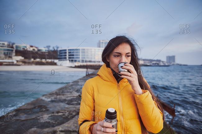 Woman on pier drinking from flask, Odessa, Odessa Oblast, Ukraine, Europe