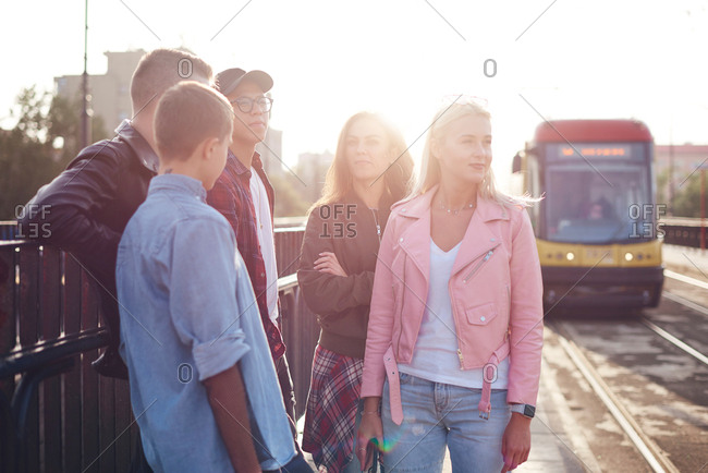 Five young adult friends waiting at sunlit city tram station
