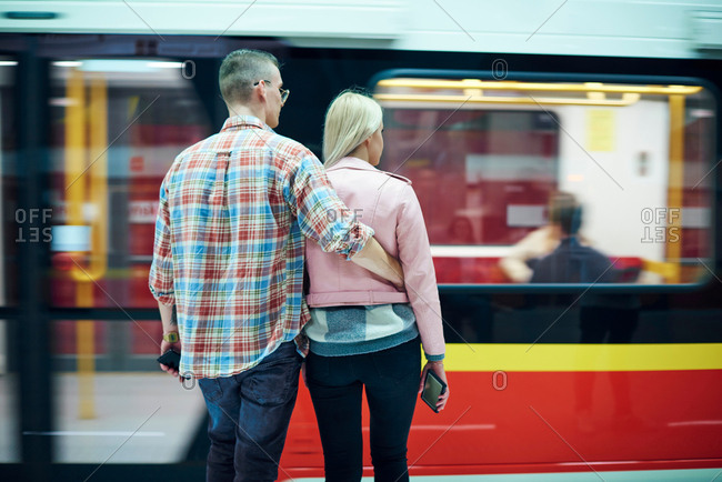 Rear view of young couple waiting at city tram station