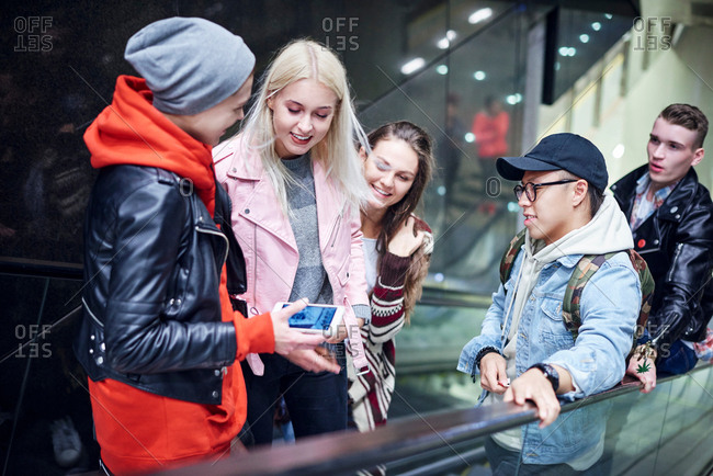 Young adult friends moving up underground station escalator  looking at smartphone