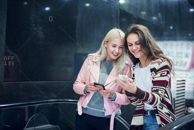 Two young women moving up underground station escalator  looking at smartphone