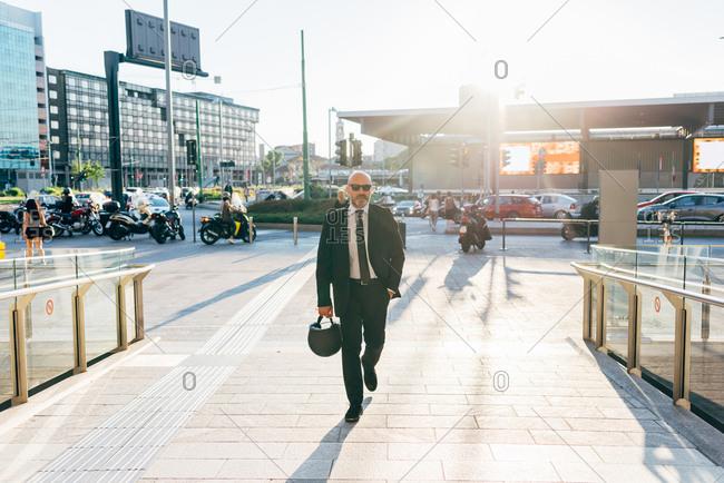 Mature businessman walking outdoors, carrying motorcycle helmet