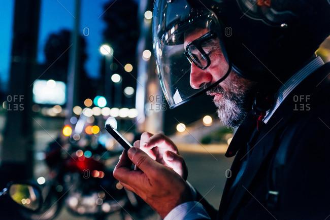 Mature businessman outdoors at night, wearing motorcycle helmet, using smartphone, profile