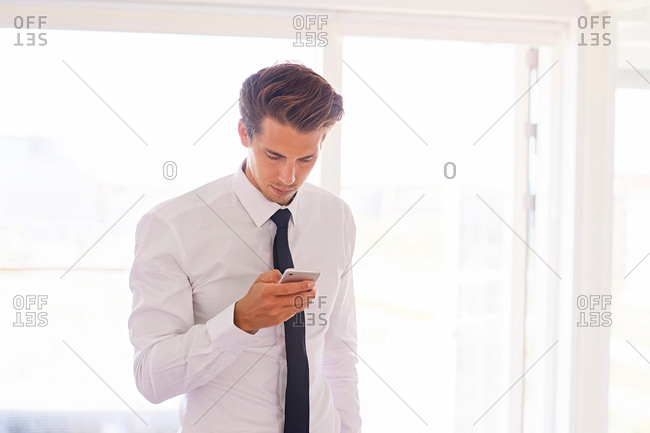 Businessman in living room looking at smartphone