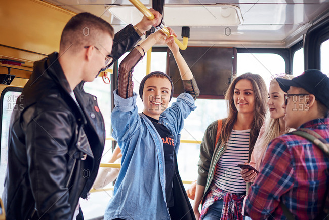 Five young adult friends chatting on city tram