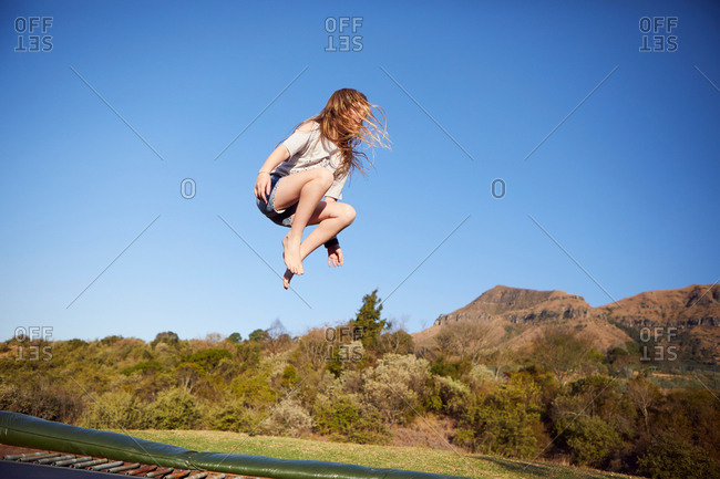 Young girl jumping on trampoline, mid air, in rural setting