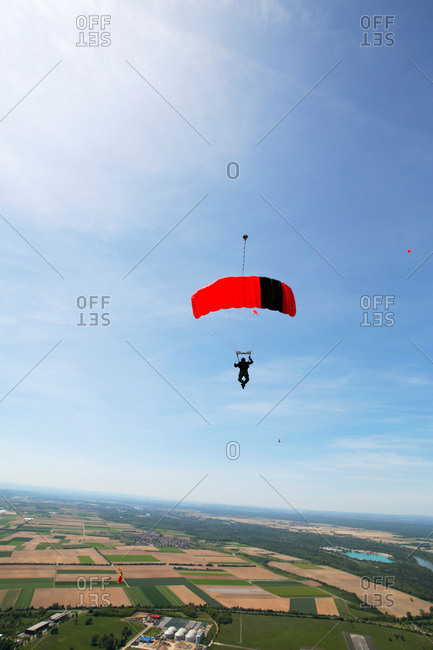 Skydiver is flying under parachute against sky over rural fields