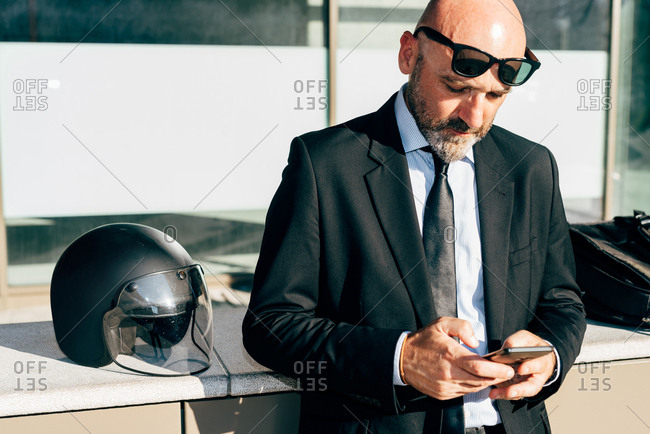 Mature businessman standing outdoors, using smartphone, motorcycle helmet on wall beside him