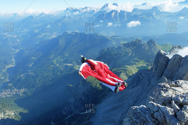 Male wingsuit BASE jumper taking off from cliff edge