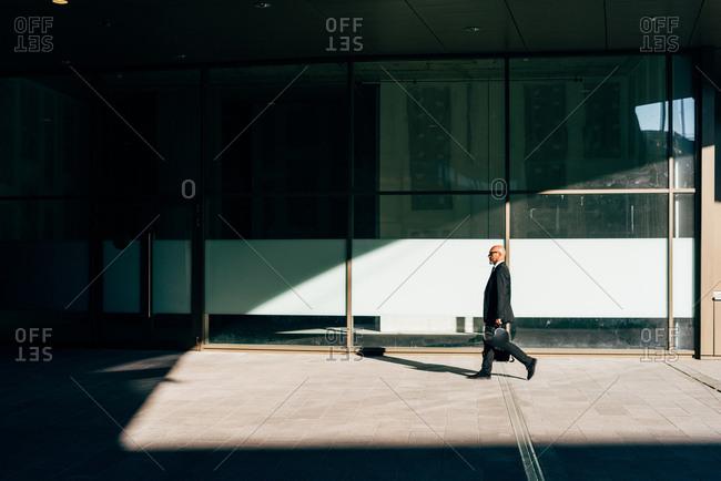 Mature businessman walking outdoors, carrying motorcycle helmet, side view