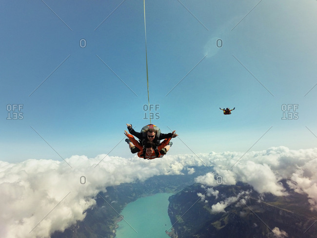 Portrait of tandem skydivers above clouds and landscape