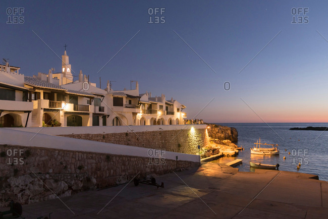 Whitewashed buildings over harbor at dusk, Mahon, Menorca, Spain