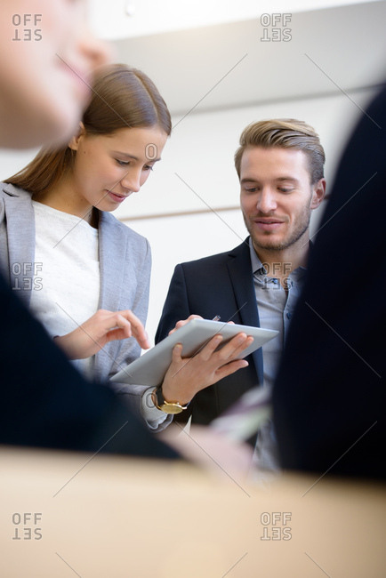 Young businesswoman and man using digital tablet touchscreen at boardroom table
