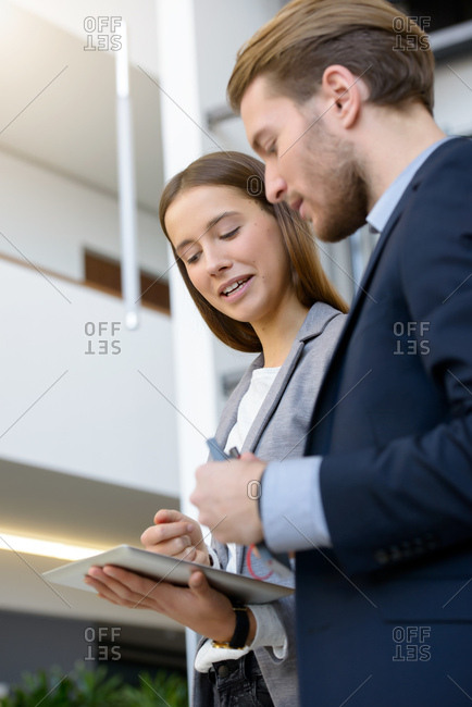 Young businesswoman and man using digital tablet in office atrium